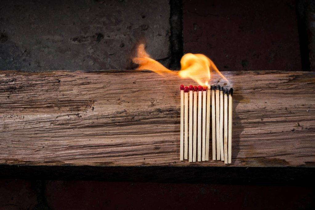 A line of matches on a log of wood, with a flame burning the matches from right to left.