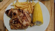 Roasted chicken with corn on the cob and fries
