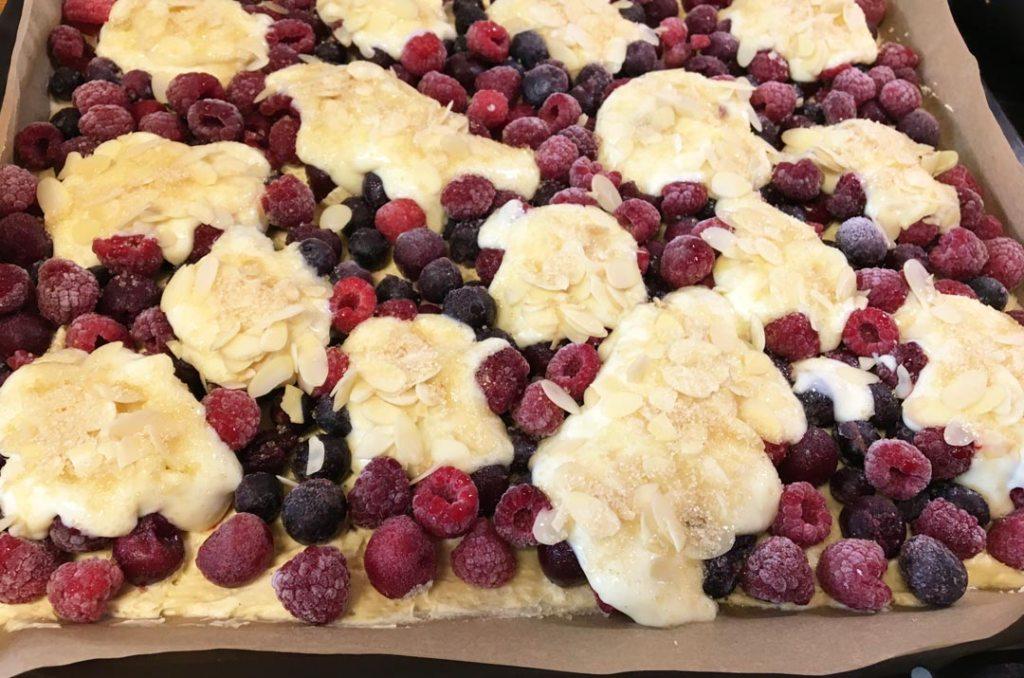 Pudding auf das Obst verteilen und mit den Mandelblättchen und dem Braunen Zucker bestreuen. Foto