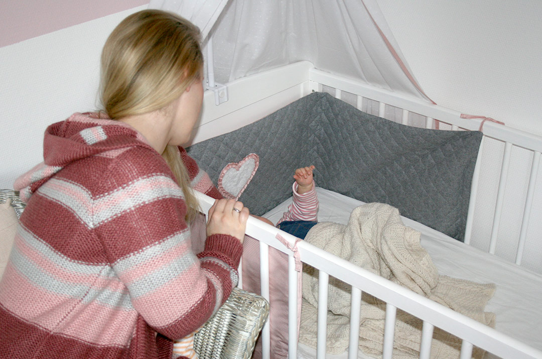 Foto von: Ich am Kinderbett meiner kleinen Tochter. Fühlen ob ihre Stirn warm ist. Darjas Welt