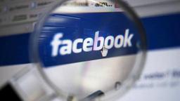 Facebook-Logo unter einer Lupe (Bild: DPA)