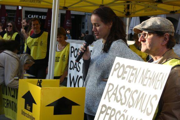 Jana Mathy ruft zum gesellschaftlichen Engagement auf. Im Hintergrund tragen sich Zuhörer in Unterschriftenlisten von Amnesty International ein. Foto: Jan-Eike Hornauer