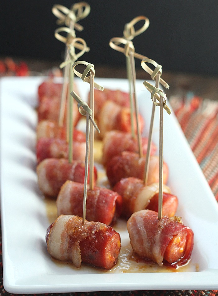 Looking for an easy appetizer with a little bit of a kick? These Bacon Wrapped Sausage Bites with Glaze are always a crowd pleaser...plus, they're ready in under 30 minutes! Perfect for game day snacks, holiday appetizers or just a snack! via @DashofEvans