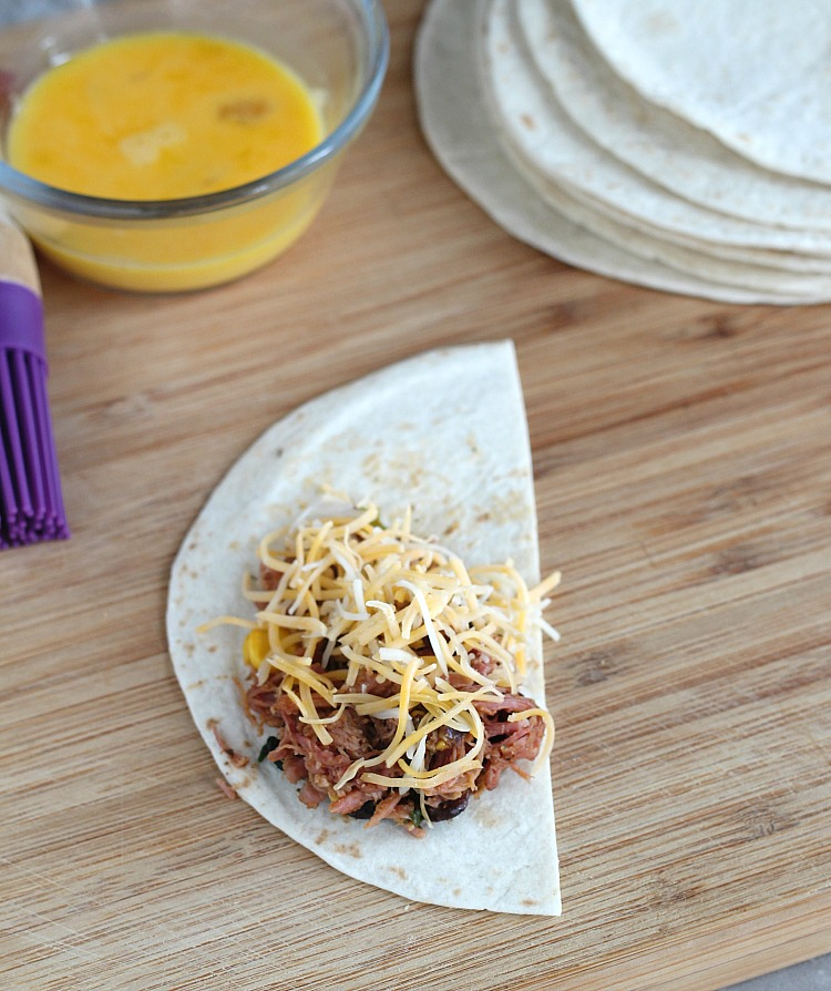 Curly's BBQ to the rescue for this easy game day snack: Southwest Pulled Pork Tortilla Triangles. Think of these as an easier to grab quesadilla! Served with a chipotle avocado ranch, these are always a crowd pleaser! via @DashOfEvans