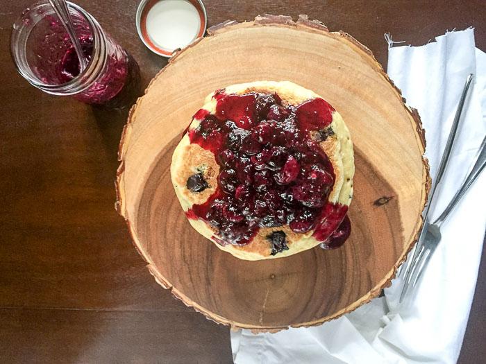 blueberry pancakes covered in fresh blueberry compote