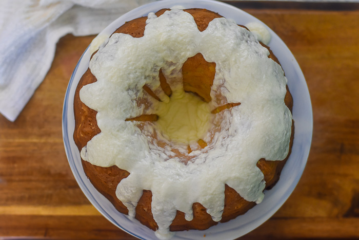 frosted pineapple pound cake on cake stand