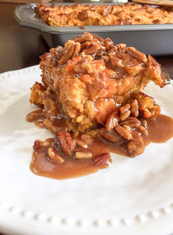 piece of sweet potato bread pudding with praline sauce over top.