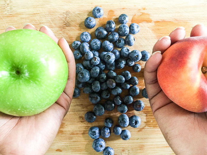 holding a green apple, peach and fresh blueberries