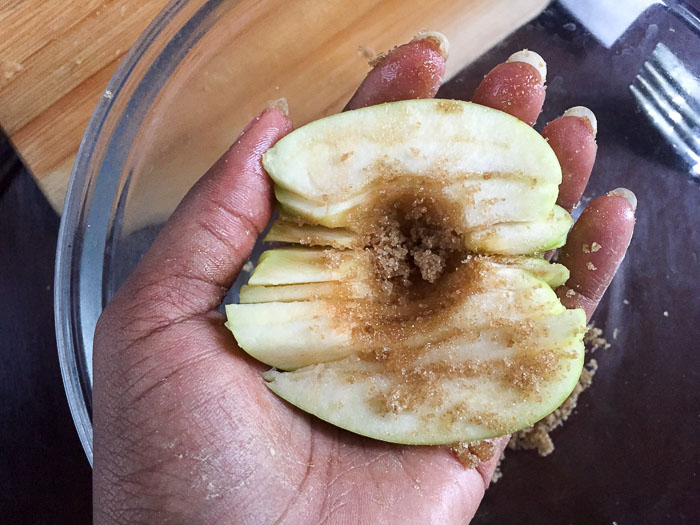 holding sliced apple covered in brown sugar