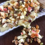 Hot Mess Harvest Dip is made with baked brie, pumpkin seeds, golden raisins, chopped honeycrisp apple, and a drizzle of honey! Get the perfect-for-fall recipe by Dash of Jazz