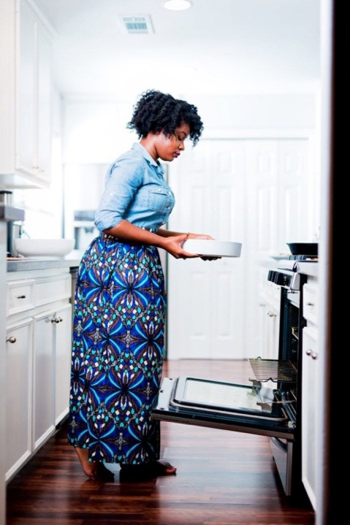 Jazzmine standing in kitchen holding dish to place into open oven