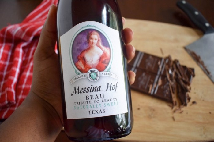 holding bottle of Messina Hof Beau wine