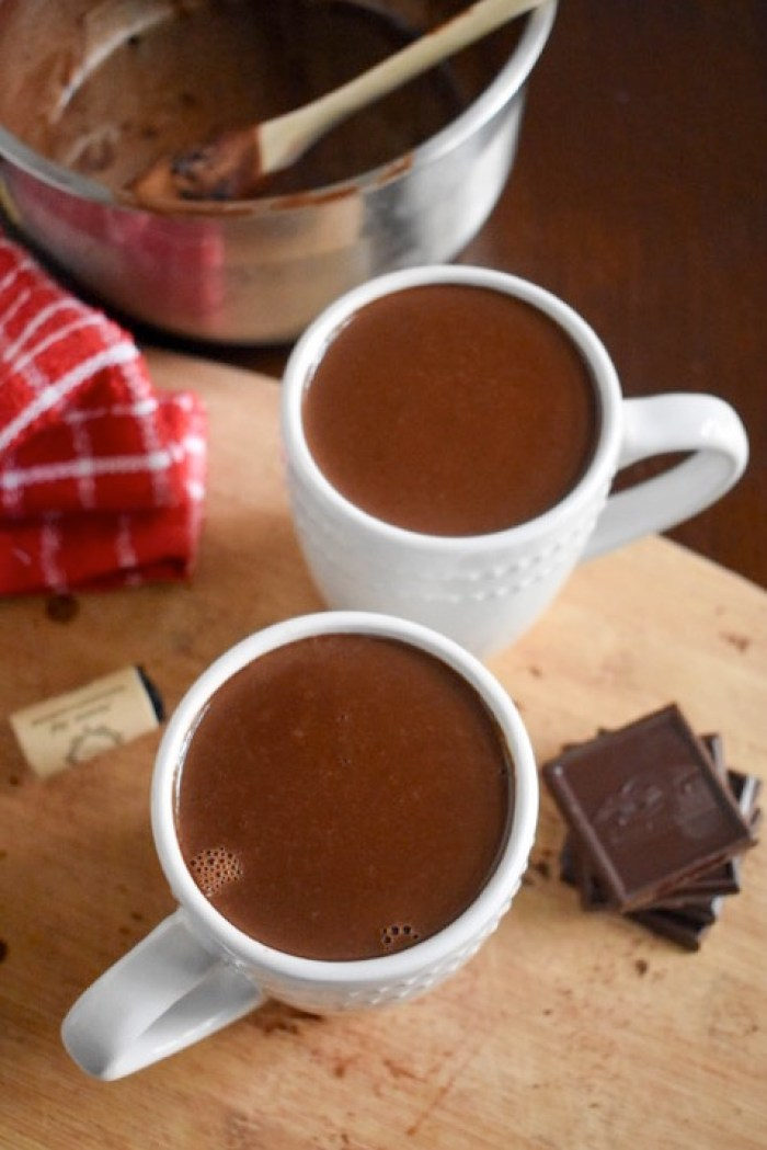 two mugs of red wine hot chocolate on cutting board