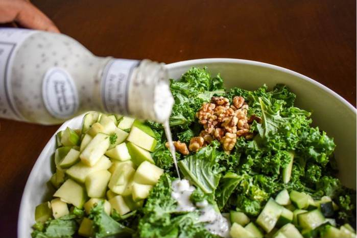 Pouring dressing over kale salad