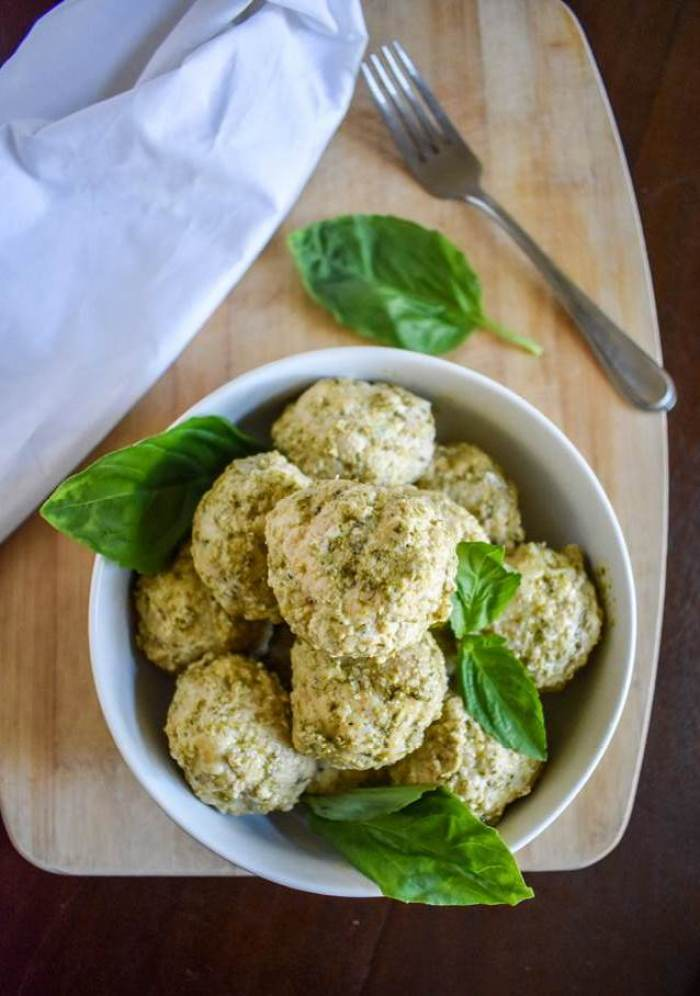pesto parmesan meatballs in bowl with fresh basil leaves