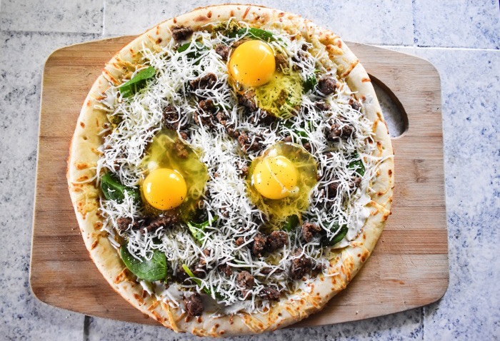 unbaked brunch pizza topped with raw eggs