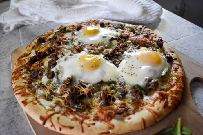 baked brunch pizza topped with runny fried eggs