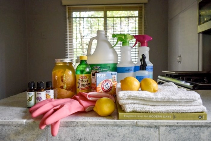 collection of natural home cleaners and tools on countertop