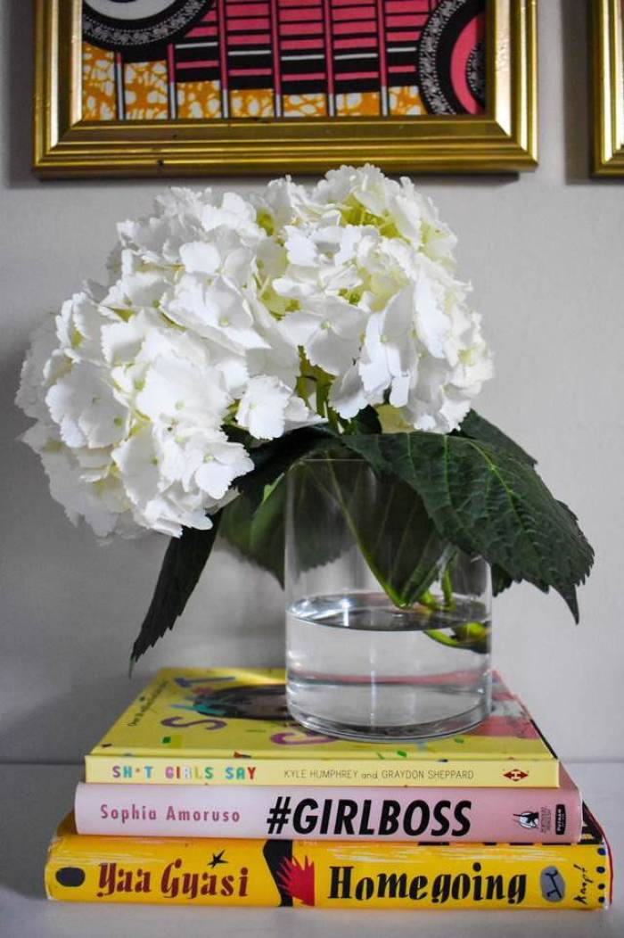 single white hydrangea in a clear vase on stack of three books