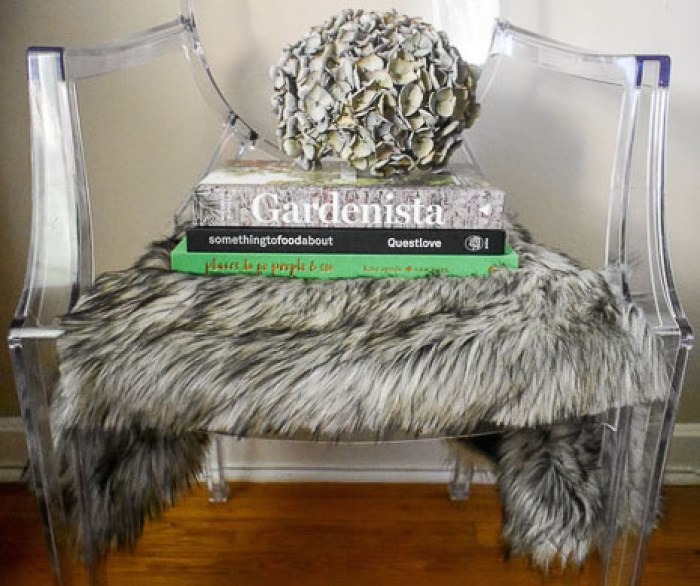 coffee table books, antique hydrangea, and fur seat cover on ghost chair