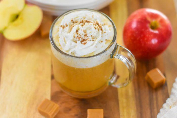 spiked caramel apple cider in a clear mug.