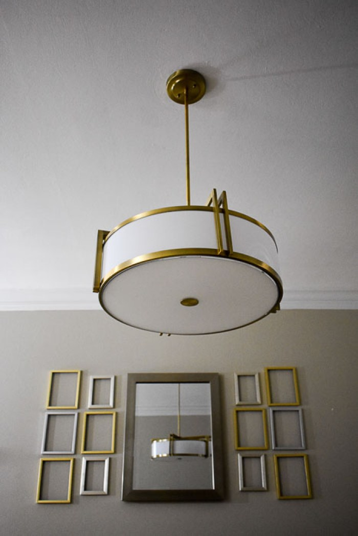 metallic empty frame gallery wall and drum pendant chandelier in finished dining room reveal