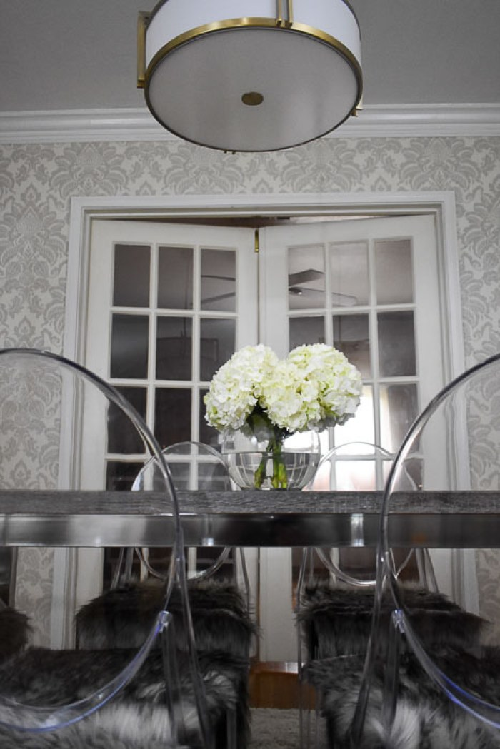 hydrangeas on gray dining table surrounded by ghost chairs