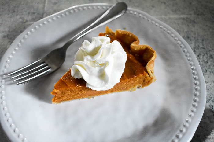 slice of sweet potato pie topped with whipped cream