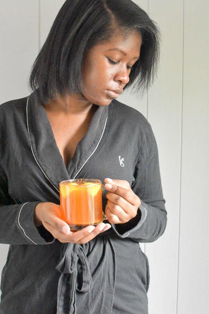 Dash of Jazz holding mug of 4-ingredient feel-better tea