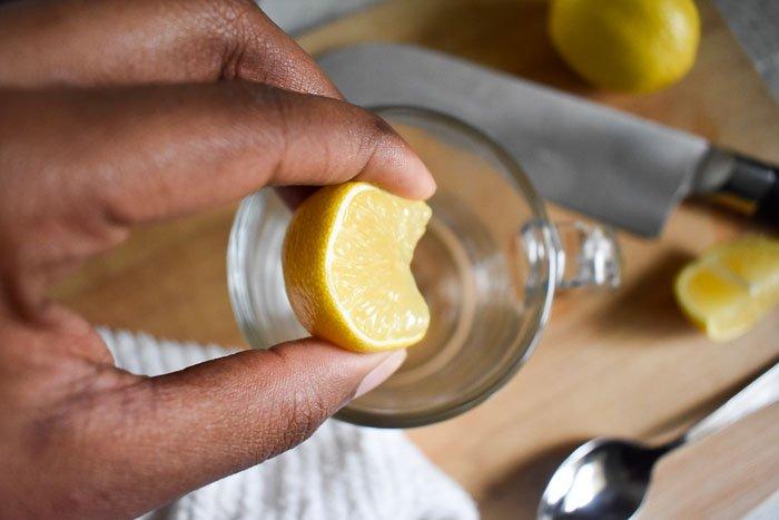 squeezing lemon into a mug