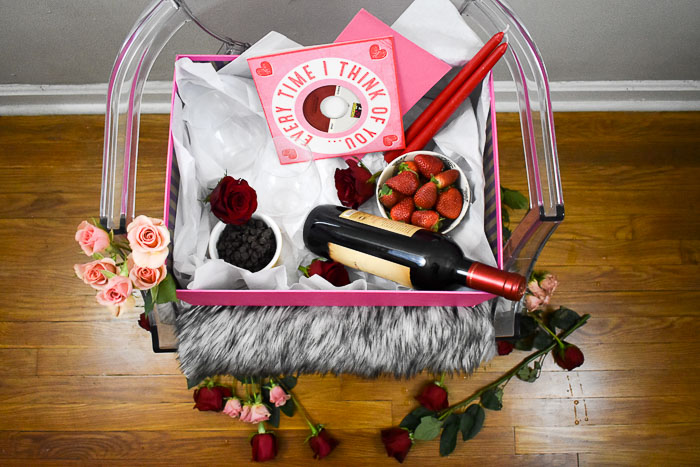 bottle of red wine, strawberries, flowers, chocolate, candles, and Valentine's Day cards in a box sitting on a ghost chair