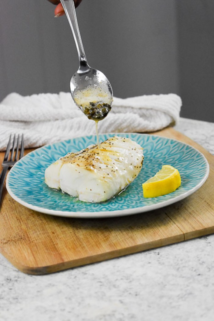 baked cod filet being drizzled with brown butter and capers