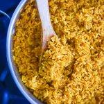 overhead view of pot of Nigerian jollof rice with wooden spoon.
