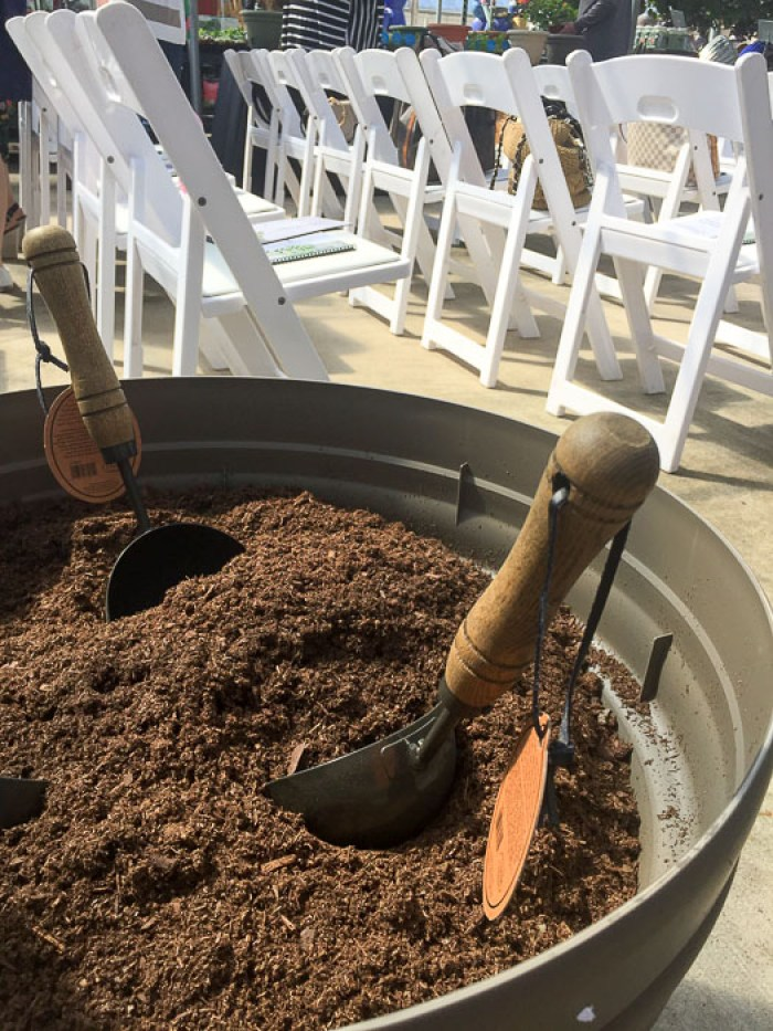 two small trowels in a large pot of soil