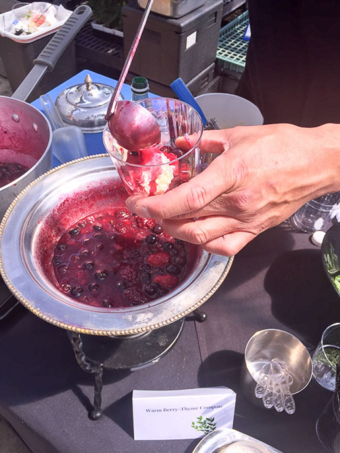 warm berry thyme compote being spooned over blue bell homemade vanilla ice cream