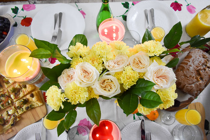 centerpiece of garden roses, yellow carnations, and green leaves on a brunch tablsecape