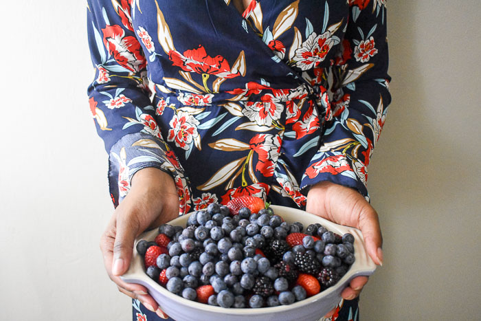woman in floral dress holding dish of fresh berries