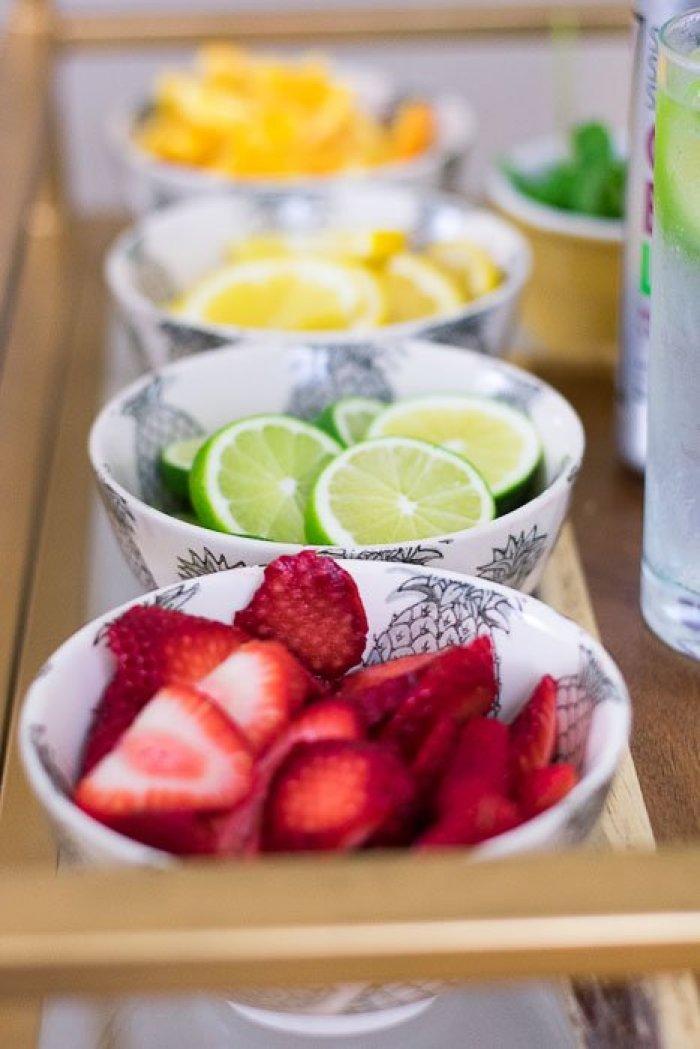 sliced fresh strawberries, limes, lemons, and oranges in bowls