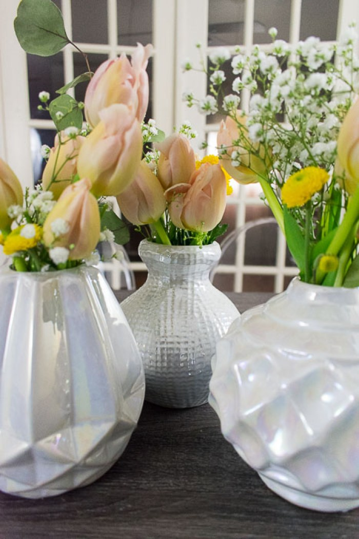 three flower arrangements in short white iridescent vases