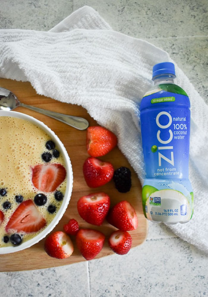 hulled strawberries between a bottle of ZICO coconut water and a smoothie bowl