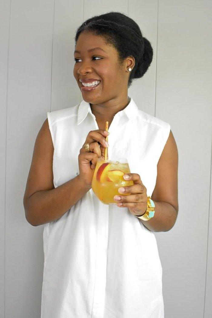 Dash of Jazz holding glass of lemon ginger bellini punch