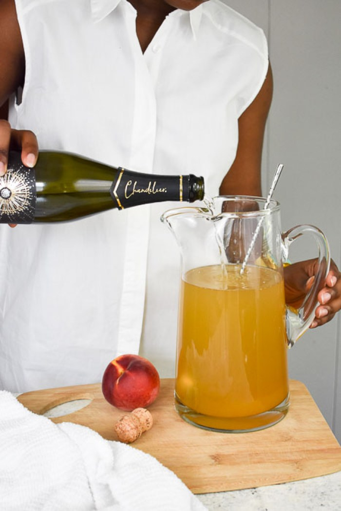 Dash of Jazz pouring sparkling wine into a pitcher of lemon ginger bellini punch