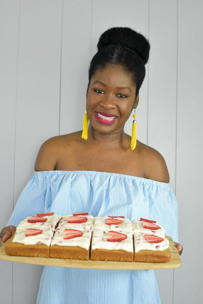 Dash of Jazz holding sliced strawberry cream cheese sheet cake