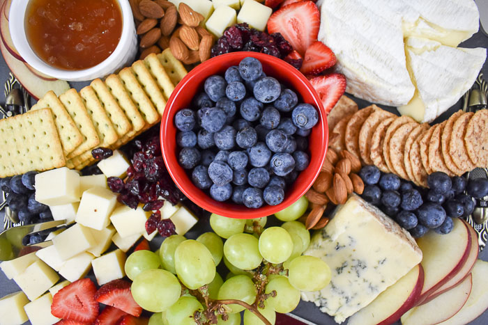 cheese board with assorted fruit, honey, crackers, and cheese