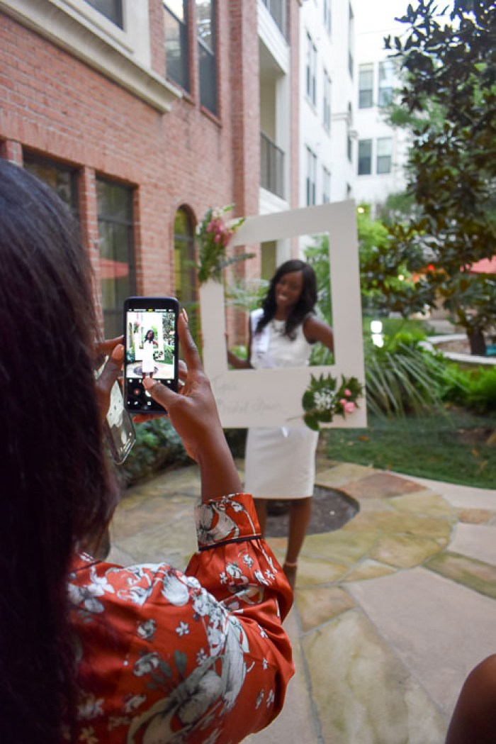 bride posing with photo booth frame at bridal shower