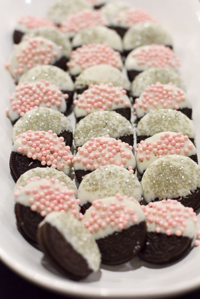 white chocolate dipped Oreos adorned with pink and silver sprinkles