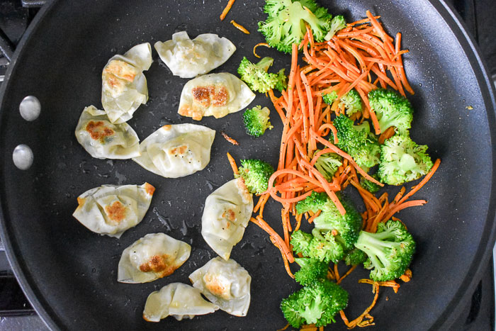 broccoli florets, matchstick carrots, and Bibigo mini wontons pan frying