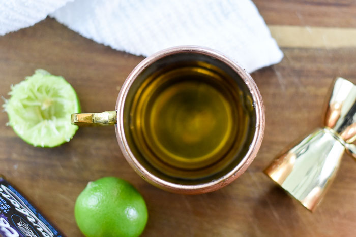 bourbon and lime juice in copper mule mug