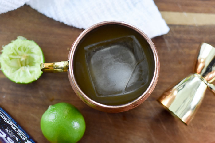 ice cube, bourbon, and lime juice in copper mug