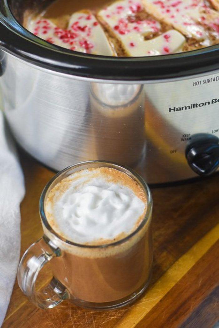 mug of peppermint hot cocoa next to crock pot